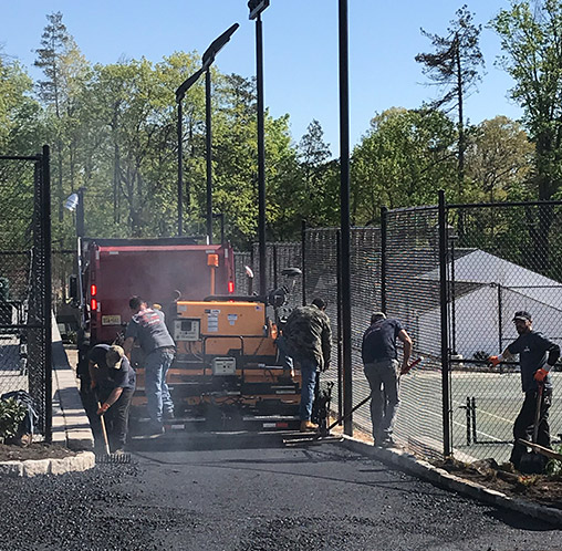 a macchione brothers employees paving a road