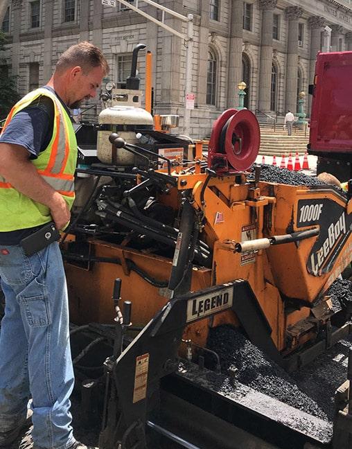 man operating asphalt paving machine