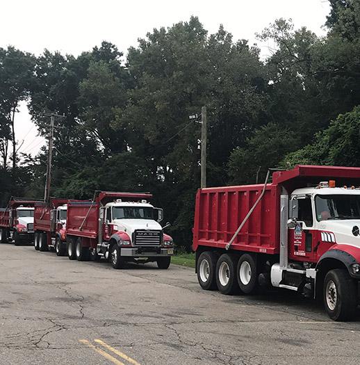 three dump trucks on road